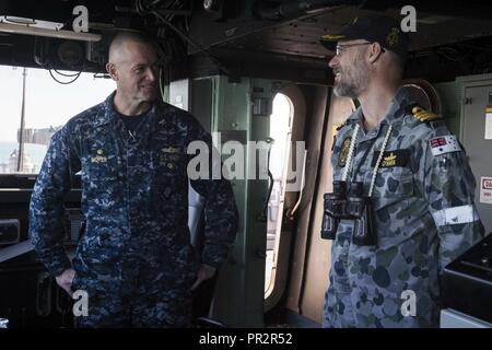 MORETON BAY (July 27, 2017) Capt. Nate Moyer, commanding officer of the amphibious transport dock USS Green Bay (LPD 20), and Royal Australian Navy Cmdr. Brendan O'Hara, from Carwoola, New South Wales, Australia, discuss ship maneuvers in the pilot house during a sea and anchor detail. Green Bay, part of the Bonhomme Richard Expeditionary Strike Group, is operating in the Indo-Asia-Pacific region to enhance partnerships and be a ready-response force for any type of contingency. - Stock Photo