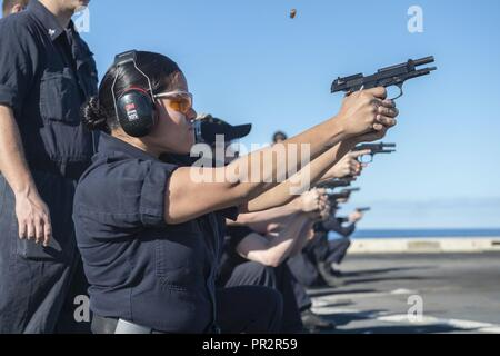 CORAL SEA (July 26, 2017) Seaman Edith Argueta, from Sioux City, Iowa, fires a 9mm service pistol during a weapon qualification on the flight deck of the amphibious transport dock USS Green Bay (LPD 20). Green Bay, part of the Bonhomme Richard Expeditionary Strike Group, is operating in the Indo-Asia-Pacific region to enhance partnerships and be a ready-response force for any type of contingency. - Stock Photo