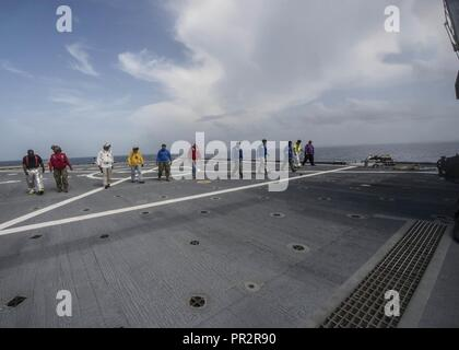 CARIBBEAN SEA (July 26, 2017) Personnel assigned to expeditionary fast transport USNS Spearhead (T-EPF-1) conduct a foreign object debris walk down of the ship's flight deck, prior to helicopter deck landing qualifications during Southern Partnership Station-Expeditionary Fast Transport 2017. SPS-EPF 17 is a U.S. Navy deployment executed by U.S. Naval Forces Southern Command/U.S. 4th Fleet, focused on subject matter expert exchanges with partner nation militaries and security forces in Central and South America. - Stock Photo