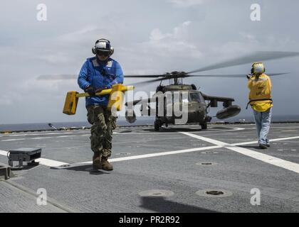 CARIBBEAN SEA (July 26, 2017) Construction Mechanic Third Class Nick Hodges, assigned to Navy Cargo Handling Battalion One, removes chocks during helicopter deck landing qualifications aboard expeditionary fast transport USNS Spearhead (T-EPF-1) in support of Southern Partnership Station-Expeditionary Fast Transport 2017. SPS-EPF 17 is a U.S. Navy deployment executed by U.S. Naval Forces Southern Command/U.S. 4th Fleet, focused on subject matter expert exchanges with partner nation militaries and security forces in Central and South America. - Stock Photo