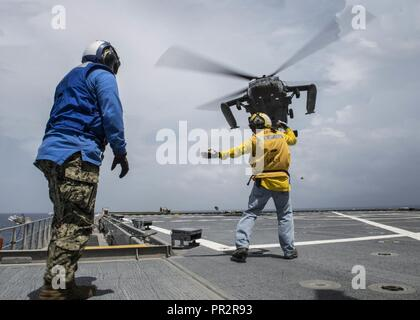 CARIBBEAN SEA (July 26, 2017) Landing Signalman Jimmy Conner, right, a civilian mariner assigned to Military Sealift Command, performs helicopter deck landing qualifications aboard expeditionary fast transport USNS Spearhead (T-EPF-1) during Southern Partnership Station-Expeditionary Fast Transport 2017. SPS-EPF 17 is a U.S. Navy deployment executed by U.S. Naval Forces Southern Command/U.S. 4th Fleet, focused on subject matter expert exchanges with partner nation militaries and security forces in Central and South America. - Stock Photo
