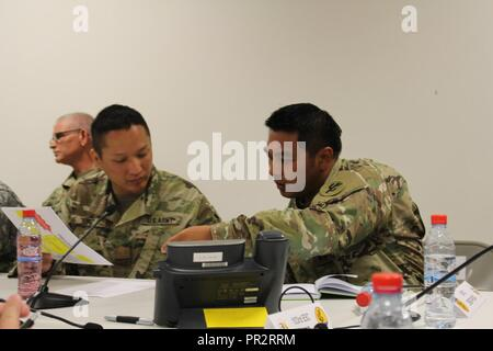 Maj. Shun Yu (left) receives information from Capt. Jason Tindungen, both operations officers for the 103rd Expeditionary Sustainment Command (ESC), during an exercise at Saber Guardian 17 at Novo Selo Training Range on July 30, 2017.  The 103rd ESC, an Army Reserve unit based out of Des Moines, Iowa, participated in Saber Guardian 17 as Mission Command to provide support of unit movement from the exercise.  Saber Guardian was a U.S. Army Europe-led, multinational exercise that spans across Bulgaria, Hungary and Romania with more than 25,000 service members from 22 allied and partner nations. - Stock Photo