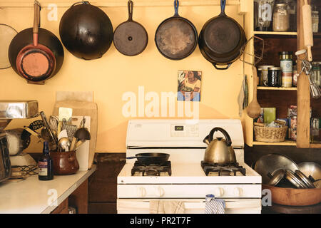 Cast iron cooking pans hanging over a white stove in an old farmhouse kitchen. Kitchen utensils are on each side. - Stock Photo
