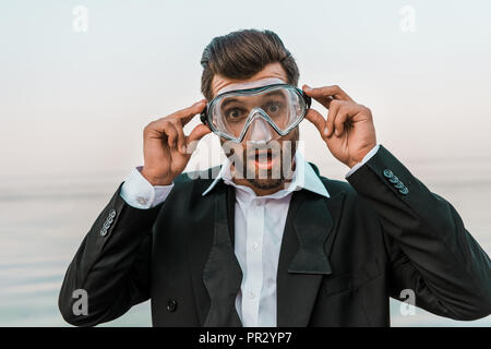 shocked man in black jacket and white shirt touching diving mask near sea - Stock Photo