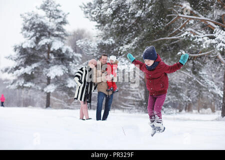 Young family with children are walking in the winter park. Winte - Stock Photo