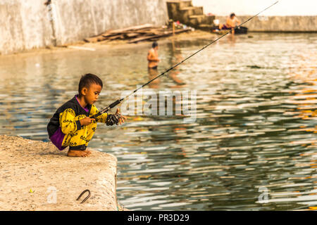 Small boy fishing on the shores of Lake Toba in Sumatra Indonesia - Stock Photo