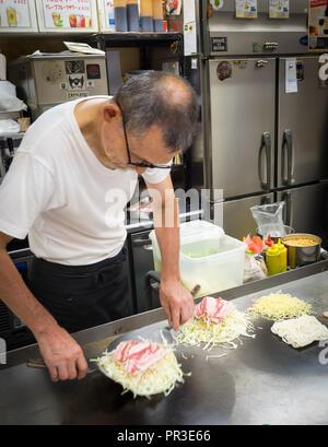 A chef makes Hiroshima style okonomiyaki at Okonomimura in Hiroshima, Japan. - Stock Photo