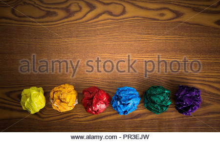 crumpled colorful paper on wooden background - Stock Photo