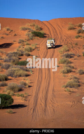 A 4WD VEHICLE MAKES IT'S WAY OVER THE RED SAND DUNES ON AN OUTBACK DIRT TRACK, NORTHERN TERRITORY, AUSTRALIA. - Stock Photo