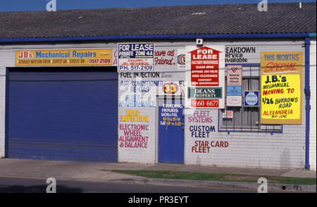 'FOR LEASE' AND ASSORTED SIGNS ON A BUILDING ONCE USED AS A GARAGE, ALEXANDRIA, INNER SYDNEY, NSW, AUSTRALIA - Stock Photo