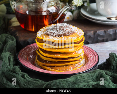 Pumpkin pancakes stack served with chocolate and coconut shreds - Stock Photo