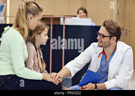 Doctor welcoming mother and daughter in clinic - Stock Photo
