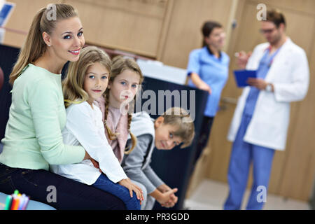 Mother and children waiting in front of registration desk in hospital - Stock Photo