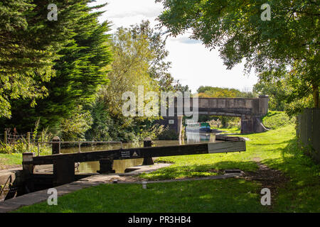 Moored narrow boat with bridge and lock on the Trent and Mersey canal in Cheshire UK - Stock Photo