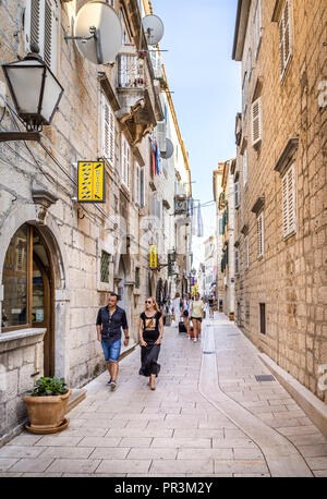 MAKARSKA, CROATIA - JULY 19, 2018: Tourists on narrow street of picturesque Makarska city, Croatia - Stock Photo