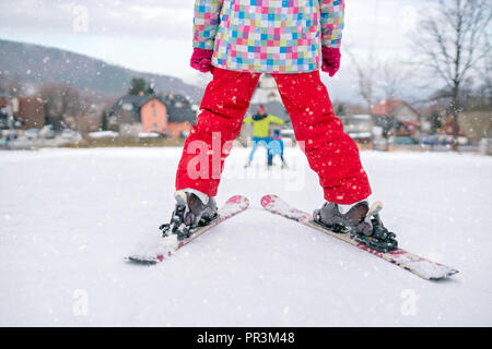 Little girl wearing red winter trousers standing on top of a small hill getting ready to ski downhill - Stock Photo