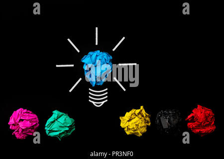 Inspiration and great idea concept. light bulb with crumpled colorful paper on black background. - Stock Photo