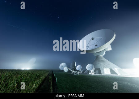 Satellite dishes at Raisting earth station in a foggy night - Stock Photo