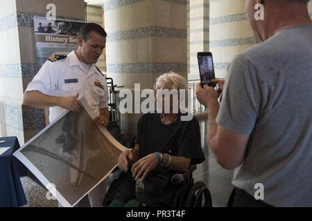 ST. PAUL, Minn. (July 22, 2017) – Lt. Luke Wolf, a native of Cary, N.C., presents Army veteran, Willard Cox, with an illustration depicting the Battle of Midway while discussing Naval heritage and history with visitors of the Minnesota Historical Society during Minneapolis/St. Paul Navy Week. Navy Week programs serve as the Navy's principal outreach effort into areas of the country without a significant Navy presence, with 195 Navy Weeks held in 71 different U.S. cities. - Stock Photo