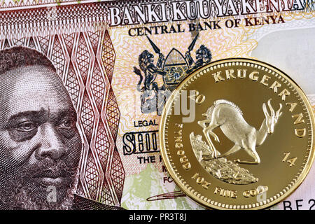 A close up image of a Kenyan fifty shilling note with a gold Krugerrand coin - Stock Photo
