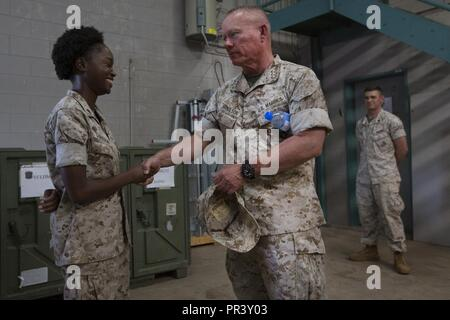 AUSTRALIAN ARMY BASE ROBORTSON BARRACKS, Australia— U.S. Marine Lt. Gen. Lawrence Nicholson, commanding general of III Marine Expeditionary Force, presents a coin to Cpl. Keyoina Torrain, supply chain administrator and operations specialist, 1st Support Battalion, 1st Marine Logistics group, Marine Rotational Force-Darwin (MRF-D), on July 26, 2017. Nicholson traveled to Australia to observe how to further improve the proficiency and quality of life to the Marines deployed in support of MRF-D. - Stock Photo