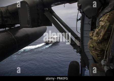 U.S. Army SGT Andrew Corbin, Standardization Instructor, 1-228th Aviation Regiment Charlie Company helps guide the UH-60 Blackhawk as it conducts deck landing qualification aboard the USNS Spearhead off the coast of Honduras in the Caribbean Sea, July 27, 2017. The 1-228th C-Company deck landing qualification consisted of classroom instruction and 5 landings with an Instructor Pilot. Once qualified each Pilot will need to maintain their currency on a scheduled timeline. - Stock Photo