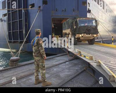 Lt. Col. Angel Estrada, Commander of Regimental Support Squadron, 2d Cavalry Regiment, watches his Soldiers load a vehicle onto a vessel in Port of Burgas, Bulgaria, July. 24,2017. - Stock Photo