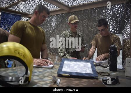 CAMP LEMMONIER, Djibouti (July 27, 2017) Constructionman 1st Class Christopher Gilbert ,left, Fire Controlman 2nd Class Adam Babica,middle, and Utilitiesman 2nd Class Tyler Scruggs , all assigned to Coastal Riverine Squadron 1, review maintenance procedures in preparation for an upcoming inspection at Camp Lemonnier, Djibouti, July 27, 2017. The Coastal Riverine Force is a core Navy capability that provides high value asset protection and maritime security operations in coastal and inland waterways. - Stock Photo