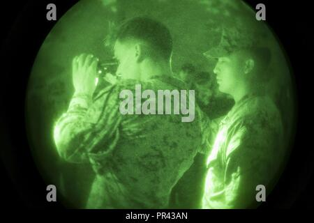 U.S. Marine Corps Sgt. Pawel Cabaj, left, bust instructor, 2nd Marine Division, demonstrates how to use a PVS-14 night vision device during Career Orientated Training for Midshipmen (CORTRAMID) Marine Week, Camp Lejeune, N.C., July 25, 2017. The purpose of CORTRAMID is to expose students to opportunities in the Fleet Marine Forces and generate an interest in a Marine Corps commission. - Stock Photo