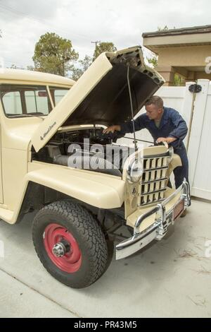 Lieutenant Colonel Timothy Silkowski, director of Fleet Support Division, adjusts the intake manifold on the carburator of his 1950 Jeep Willys Station Wagon, aboard Marine Corps Logistics Base Barstow, Calif., July 25. He found the vehicle abandoned and burried up to the wheel wells in sand, and has worked diligently to restore it in his free time. - Stock Photo