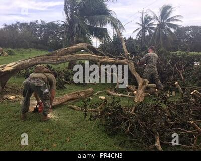 TINIAN, Commonwealth of the Northern Marianas Islands - U.S. Marines with Marine Air Control Group 18 and Navy Seabees with 30th Naval Construction Regiment clear debris from Typhoon Mangkhut on Tinian Sept. 11, 2018. Typhoon Mangkhut struck the Commonwealth of the Northern Marianas Islands September 10. Service members from Indo-Pacific Command are providing Department of Defense support to the Federal Emergency Management Agency (FEMA), and working with Guam and Commonwealth of the Northern Mariana Islands' civil and local officials for typhoon recovery efforts. - Stock Photo