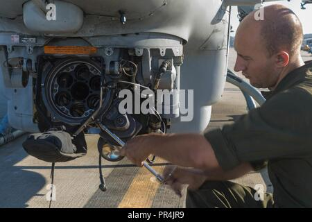 U.S. Marine Corps Lance Cpl. Antony Thompson, ordinance technician, Marine Light Attack Helicopter Squadron 775, 4th Marine Aircraft Wing, unscrews a bolt during an inspection of a M197 turret mounted on a Bell AH-1Z Viper Attack Helicopter at Marine Corps Air Station Camp Pendleton, California, Sept. 14, 2018. Turret inspections are conducted every 56 days. - Stock Photo