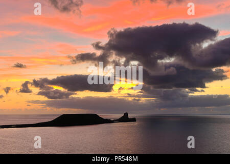 Rhossili, Wales, UK.  29th September 2018. UK Weather.   A moody sunset over Worms Head viewed from Rhossili in the Gower peninsular in Wales.  Picture Credit: Graham Hunt/Alamy Live News - Stock Photo