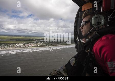 A pararescueman assigned to the 334th Air Expeditionary Group scans the coastline, Sept. 16, 2018, in the skies over South Carolina. The 334th AEG is an expeditionary search and rescue unit which is pre-positioned to provide relief in the wake of tropical storm Florence. Comprised of 23d Wing and 920th Rescue Wing personnel and assets, the 334th AEG is ready to perform surface, fixed wing and rotary SAR operations when needed. - Stock Photo