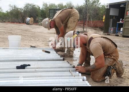 U.S. Navy Equipment Operator 3rd Class Beau Schramm (left) and Utilitiesman 2nd Class Anthony Calleja (right), assigned to Naval Mobile Construction Battalion (NMCB) 133, clean and tape pipe ends in Riohacha, Colombia, Sept. 11, 2018, during water-well drilling exploration operations as part of Southern Partnership Station 2018. Southern Partnership Station is a U.S. Southern Command-sponsored and U.S. Naval Forces Southern Command/U.S. 4th Fleet-conducted annual deployment focused on subject matter expert exchanges and building partner capacity in a variety of disciplines including medicine,  - Stock Photo