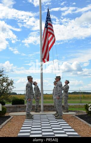 Airmen with the 181st Intelligence Wing lower the flag during a retreat ceremony at Hulman Field Air National Guard Base, Terre Haute, Indiana, Sep. 16, 2018. - Stock Photo