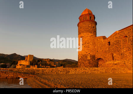 The church of Notre-Dames-des-Anges and the Château Royal at Collioure glowing in the early morning light. - Stock Photo
