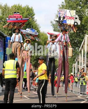 London, UK - August 27, 2018:  Notting Hill Carnival Colorful stilt walkers dancing