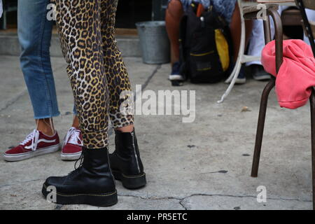 Detail young woman boots and teenage legs in sneakers jeans standing - Stock Photo