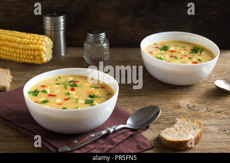 Homemade Corn Chowder Soup in white bowl. Vegetarian creamy corn soup with greens and vegetables. - Stock Photo