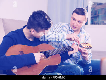 Guy with his father are resting and playing on guitar at the home. - Stock Photo