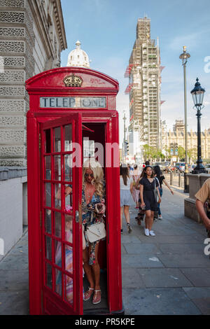 London, England - August 4, 2018: Woman and child exiting a red traditional telephone booth in London and Big Ben Clock Tower under maintenance in the - Stock Photo