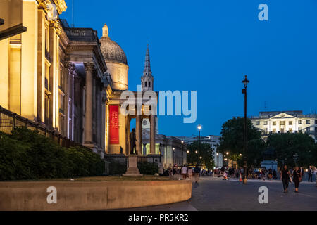 London, England - August 4, 2018: Evening side-view of the National Gallery at Trafalgar Square, London, as people stroll by. - Stock Photo