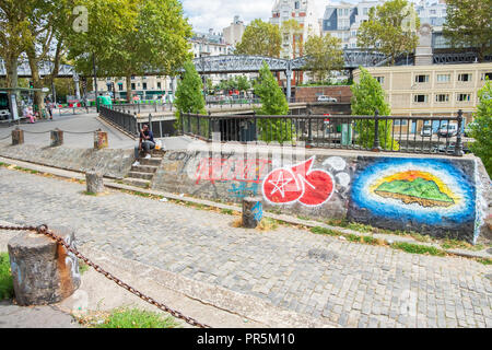 Paris, France - August 8, 2018: Man sitting on the steps off Jean Jaures avenue in north Paris. - Stock Photo