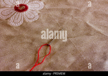 red thread inserted into a needle on the background of linen fabric with a pattern. Copy space. Free space for text, Close-up, top view - Stock Photo
