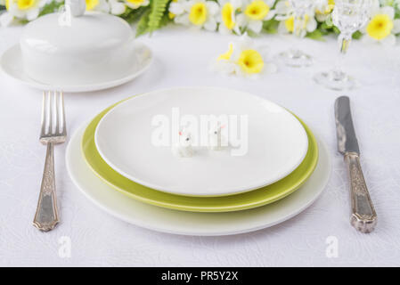 Classic serving for a Easter dinner with white and green porcelain plates, silverware and spring flowers on a white tablecloth - Stock Photo