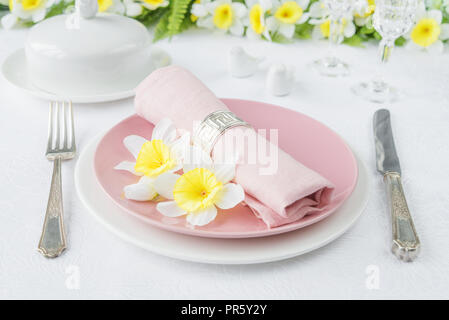 Classic serving for a Easter dinner with white and pink porcelain plates, silverware and spring flowers on a white tablecloth - Stock Photo