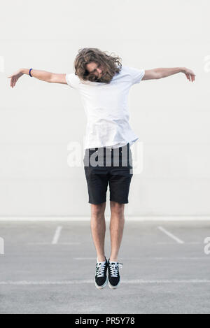 Young man in a Jesus Christ suspended pose concept - Stock Photo