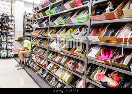 Miami Florida Kendall The Palms at Town & Country Mall Nordstrom Rack inside shopping display sale women's shoes shoe boxes boy sitting texting - Stock Photo