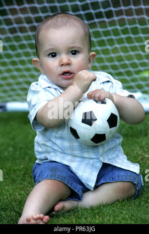 toddler playing with football - Stock Photo